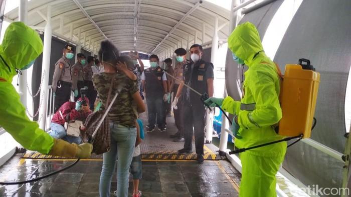 Petugas menyemprotkan disinfektan ke TKI yang tiba di Pelabuhan Internasional Batam (Agus Siagian/detikcom)
