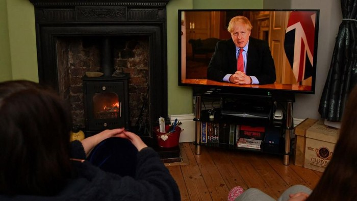Members of a family listen as Britains Prime Minister Boris Johnson makes a televised address to the nation from inside 10 Downing Street in London, with the latest instructions to stay at home to help contain the Covid-19 pandemic, from a house in Liverpool, north west England on March 23, 2020. - Britain on Monday ordered a three-week lockdown to tackle the spread of coronavirus, shutting