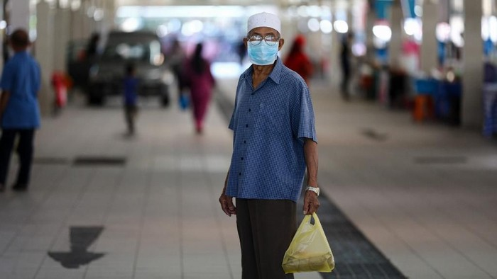A man wearing a face mask, amid concerns over the spread of the COVID-19 coronavirus, holds a plastic bag of goods at the Gadong Night Market in Bandar Seri Begawan on March 16, 2020. (Photo by Dean KASSIM / AFP)