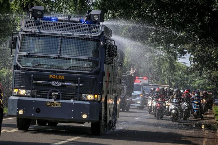 Petugas kepolisian Polresta Tangerang menyemprotkan cairan disinfektan menggunakan mobil Armor Water Canon (AWC) di Tigaraksa, Kabupaten Tangerang, Banten, Selasa (24/3/2020). Penyemprotan cairan disinfektan di wilayah tersebut dilakukan guna mengantisipasi penyebaran COVID-19. ANTARA FOTO/Fauzan/nz