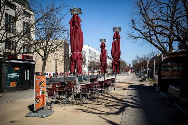 Jalan-jalan kosong dan restoran terlihat tutup di ujung Unter den Linden, Berlin, Jerman. Virus corona dan penyakit yang ditimbulkannya, COVID-19, memiliki dampak mendasar pada masyarakat, pemerintah dan ekonomi di Jerman, Kehidupan publik telah dibatasi pada hal-hal penting dalam upaya oleh otoritas untuk memperlambat penyebaran virus itu. Getty Images/Maja Hitij.