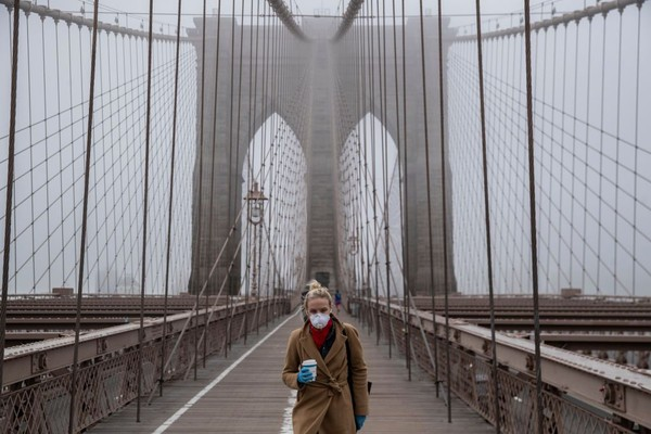 Seorang warga melintas di jembatan Brooklyn yang sepi akibat wabah Covid 19. Getty Images/Victor J. Blue.