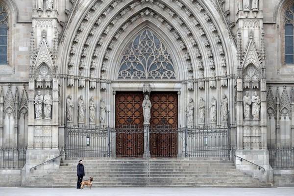Seorang wanita mengajak anjingnya berjalan-jalan di Katedral Barcelona (Catedral de la Santa Creu i Santa Eulalia) ketika negara itu berupaya menghentikan penyebaran virus Corona.Warga di Spanyol harus tinggal di rumah kecuali pergi bekerja tetapi direkomendasikan bekerja di rumah. Jumlah orang yang dipastikan terinfeksi virus corona (COVID-19) di Spanyol telah meningkat menjadi setidaknya 28.603, dengan jumlah kematian terakhir mencapai 1.756. Getty Images/Sandra Montanez.