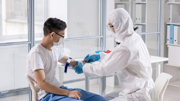Young Chinese man in mask sitting in lab while doctor in protective coveralls taking his blood in syringe for analysis