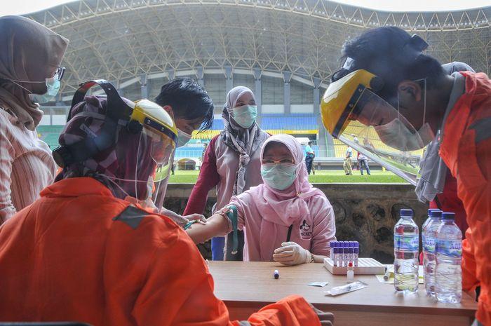 Petugas medis mengecek kesehatannya dengan mengambil sampel  darah dengan metode rapid test (pemeriksaan cepat) di Stadion Patriot Candrabhaga, Bekasi, Jawa Barat, Rabu (25/3/2020). Pemeriksaan yang dilakukan khusus tenaga medis di Bekasi guna memutus mata rantai penyebaran virus COVID-19. ANTARA FOTO/ Fakhri Hermansyah/hp.