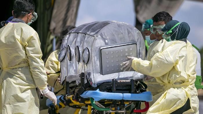 Tim medis menurunkan pasien positif terjangkit COVID-19 dari pesawat Hercules C-130 untuk dimasukkan kedalam mobil ambulas, saat simulasi pemindahan pasien COVID-19 di Bandara Hang Nadim, Batam, Kepulauan Riau, Kamis (26/3/2020). Simulasi tersebut untuk melihat kesiapan personel medis dalam menangani proses pemindahan pasien khusus Corona (COVID-19) dari  pesawat untuk dibawa ke RS Khusus Corona di Pulau Galang, Batam. ANTARA FOTO/M N Kanwa/ama.