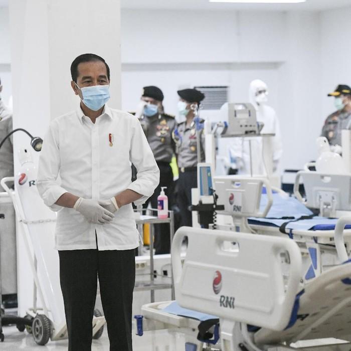 Presiden Joko Widodo merapikan masker yang digunakannya saat meninjau Rumah Sakit Darurat Penanganan COVID-19 Wisma Atlet Kemayoran, Jakarta, Senin (23/3/2020). Presiden Joko Widodo memastikan Rumah Sakit Darurat Penanganan COVID-19 Wisma Atlet Kemayoran siap digunakan untuk menangani 3.000 pasien. ANTARA FOTO/Hafidz Mubarak A/Pool/aww.