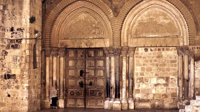 Seorang peziarah berdoa di depan pintu masuk Gereja Makam Kudus Yerusalem yang ditutup imbas pandemi COVID-19 (Foto: Ahmad GHARABLI/AFP)