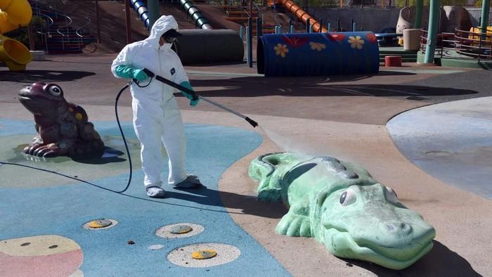 Centennial Hills Park di Las Vegas, Nevada, disemprot disinfektan untuk mencegah penyebaran Covid-19. Peralatan bermain hingga patung buaya dan katak ikut disemprot.