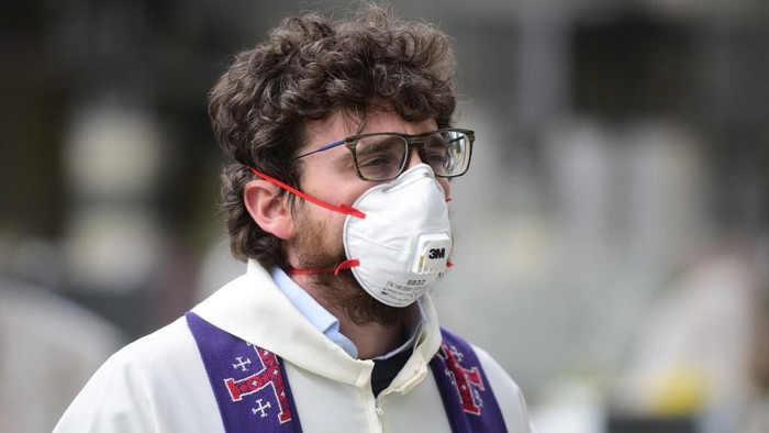 A priest wears a FPP3 face mask during a funeral ceremony at the cemetery of Grassobbio, Lombardy, on March 23, 2020, during the COVID-19 new coronavirus pandemic. (Photo by Piero CRUCIATTI / AFP)