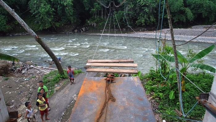 Anak-anak berada di dekat pembangunan jembatan gantung yang putus akibat banjir bandang di atas sungai Cikaniki, Kabupaten Bogor, Jawa Barat, Kamis (12/3/2020). Warga dengan dana swadaya membangun kembali jembatan gantung tersebut karena merupakan jalan utama bagi warga kampung Tonjong, Desa Karehkel, Kecamatan Rumpin dan kampung Kantalarang, Desa Leuwibatu, Kecamatan Leuwiliang untuk beraktivitas. ANTARA FOTO/Arif Firmansyah/hp.
