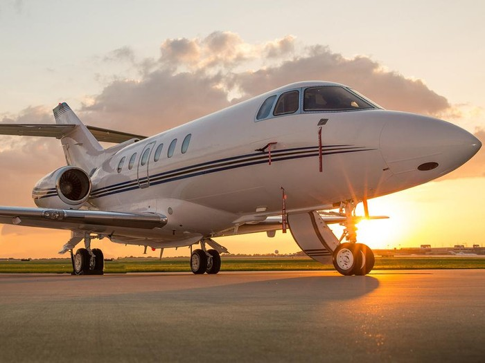 Corporate business jet setting on ramp with door open and sun setting in the background.