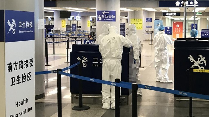 This photo taken on March 21, 2020 shows staff wearing protective suits at the health check in the international departures area of Beijing airport. - China lifted tough restrictions on the province at the epicentre of the coronavirus outbreak on March 25 after a months-long lockdown as the country reported no new domestic cases. (Photo by LAURENT THOMET / AFP)