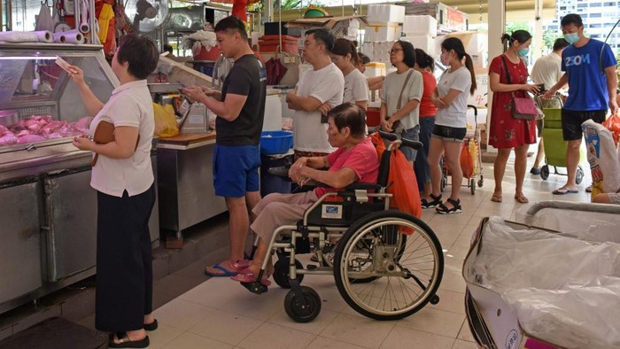 Customers, some wearing face masks as a preventive measure against the COVID-19 novel coronavirus, queue to buy meat at a market in Singapore on March 22, 2020. (Photo by Catherine LAI / AFP)