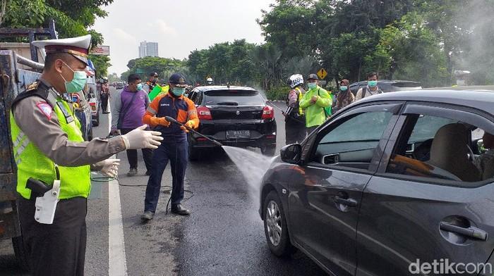 Kendaraan roda empat yang masuk ke Kota Surabaya harus antre disemprot disinfektan. Itu dilakukan untuk menekan penyebaran virus corona.