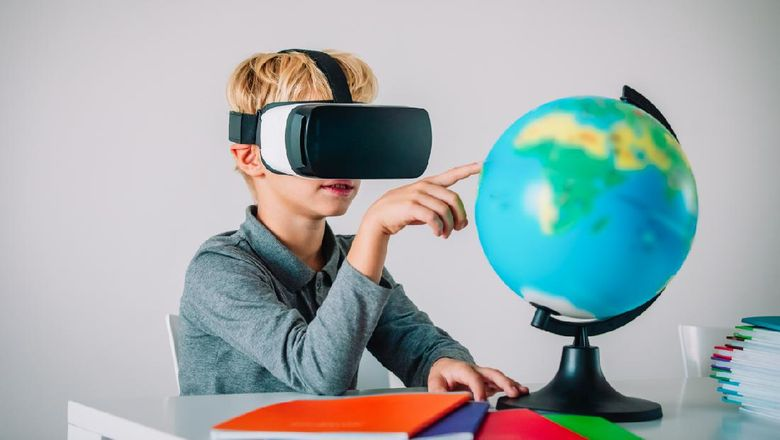 Young kid with virtual reality headset touching earth globe, technology in education