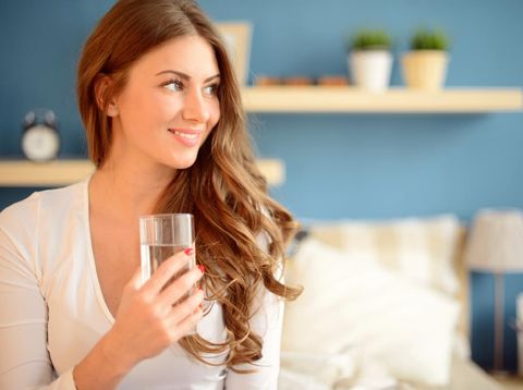 beautiful young woman holding a glass of water