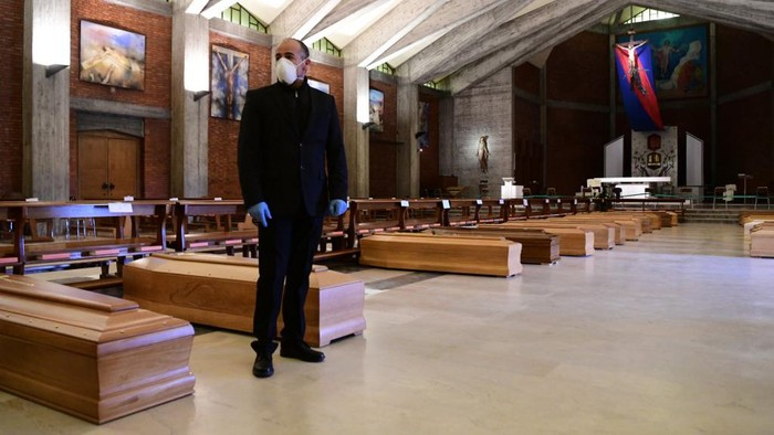A pallbearer stands next to coffins of deceased people stored prior to be cremated in the church of San Giuseppe in Seriate, near Bergamo, Lombardy, on March 26, 2020, during the countrys lockdown following the COVID-19 new coronavirus pandemic. (Photo by Piero CRUCIATTI / AFP)