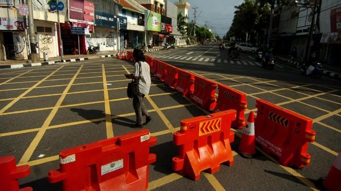 Seorang warga melintas di samping pembatas jalan di kawasan  perempatan Alun-alun Kota Tegal, Jawa Tengah, Jumat (27/3/2020). Sejak diberlakukan  penutupan jalan masuk ke Alun-alun Kota Tegal  dan pengalihan jalur di sejumlah jalan protokol untuk antisipasi penyebaran COVID-19 lima hari lalu, jalanan di pusat kota llengang dan  penjualan  sejumlah toko dan rumah makan diperkirakan menurun hingga 80 persen. ANTARA FOTO/Oky Lukmansyah/nz