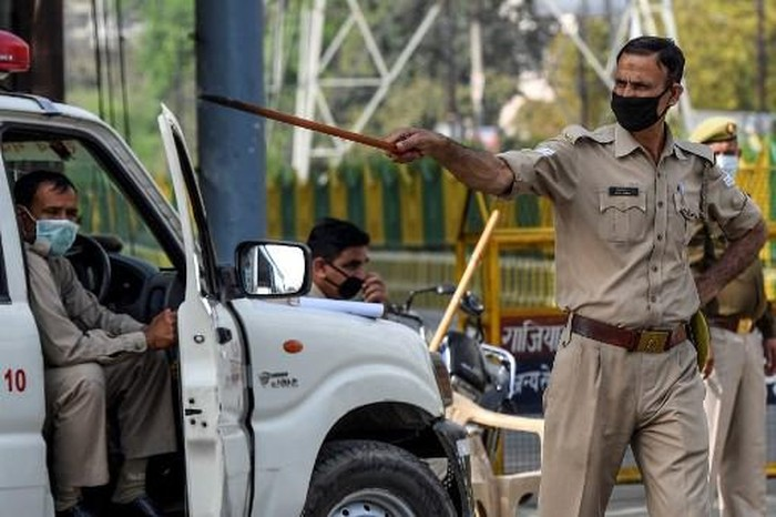 A police personnel instructs a motorist to go back at a checkpoint during a government-imposed lockdown as a preventive measure against the spread of the COVID-19 novel coronavirus, in Ghaziabad on March 24, 2020. (Photo by Prakash SINGH / AFP)