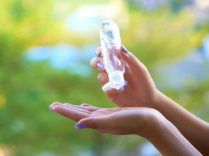 Womens hands using hand sanitizer gel . healthcare and medical .