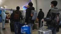 Sejumlah penumpang mengantre untuk diperiksa kesehatannya saat tiba di Wuhan.
