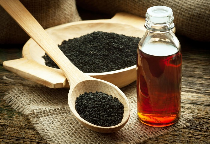 Nigella sativa (Black cumin) on wooden spoon and essential oil. Real oil from nigella looks like dark honey
