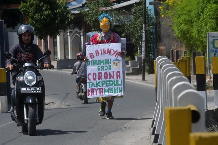 Seorang pria kenakan kostum badut saat berkeliling kawasan Palu, Sulteng. Hal itu ia lakukan sebagai bentuk kepedulian pencegahan penyebaran virus Corona.