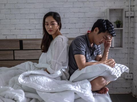 Young couple in love lying on bed at home and cuddling, embracing and enjoying weekend together