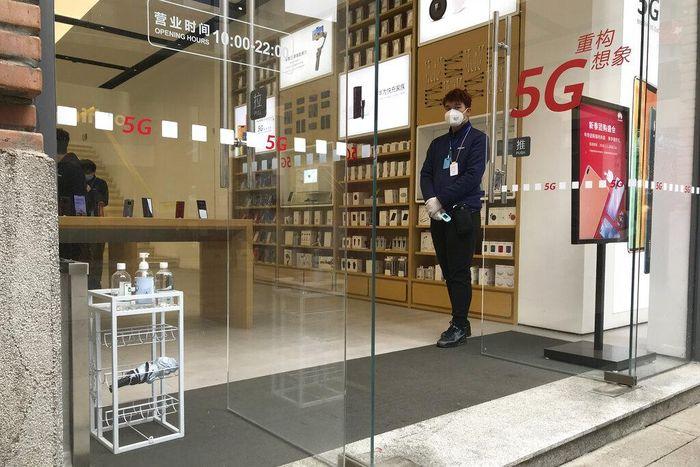Seorang petugas toko tampak bersiaga di dekat pintu masuk untuk menyapa para pengunjung yang datang ke toko yang kembali buka usai sebelumnya ditutup sementara guna mencegah penyebaran virus Corona di kawasan Wuhan, China, Senin (30/3/2020). AP Photo/Olivia Zhang.