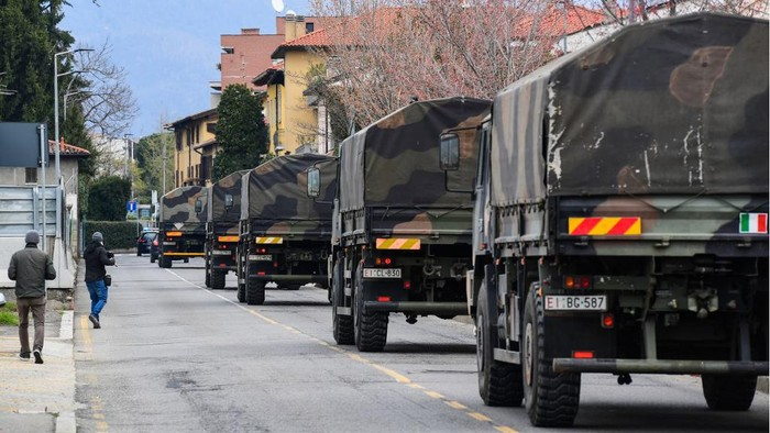 Italian Army trucks transporting coffins of victims of coronavirus cross the city of Bergamo, Lombardy, after leaving the Monumental Cemetery on March 26, 2020, to bring the coffins to crematoriums in other regions where municipalities have made themselves available to accept them, during the countrys lockdown following the COVID-19 new coronavirus pandemic. (Photo by Miguel MEDINA / AFP)