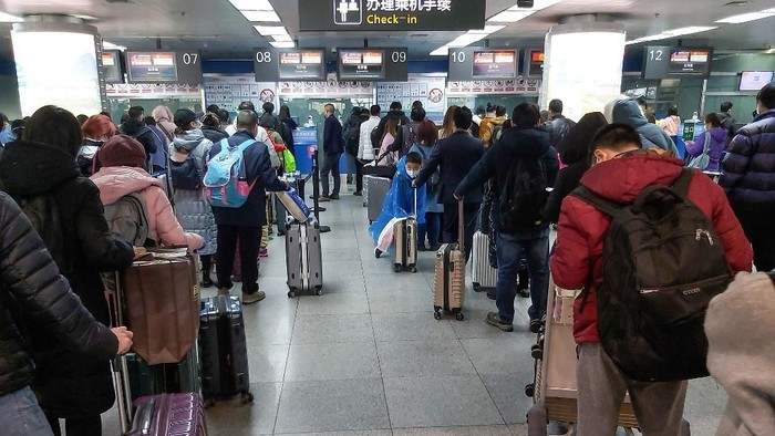 This photo taken on March 29, 2020 passengers wearing face masks, amid concerns of the COVID-19 coronavirus, queueing up to check-in before boarding flights at Yichang Sanxia Airport in Yichang in Chinas central Hubei province. - Airports in Hubei, except Wuhan Tianhe Airport, reopened for domestic flights on March 29 as travel restrictions have been loosened with official figures now routinely showing no new domestic infections. (Photo by STR / AFP) / China OUT