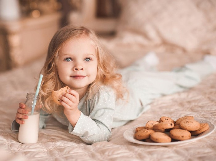 Sweet baby girl 3-4 year old eating cookies and drinking milk lying in bed close up. Good morning. Breakfast.