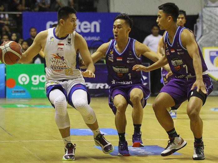 Pebasket Satria Muda Pertamina Avan Saputra (kiri) dihadang pebasket Amartha Hangtuah Sevly Rondonuwu (tengah) dan Lucky Abdi Pasondok, saat pertandingan seri keenam Indonesian Basketball League (IBL) Pertamax 2020 di DBL Arena, Surabaya, Jawa Timur, Sabtu (7/3/2020). Satria Muda Pertamina mengalahkan Amartha Hangtuah dengan skor akhir 83-79. ANTARA FOTO/Moch Asim/ama.