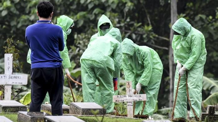 Petugas pemakaman menurunkan peti jenazah pasien COVID-19 di TPU Pondok Ranggon, Jakarta, Senin (30/3/2020). Juru bicara pemerintah untuk penanganan COVID-19 Achmad Yurianto per Senin (30/3/2020) pukul 12.00 WIB menyatakan jumlah pasien positif COVID-19 di Indonesia telah mencapai 1.414  kasus, pasien yang telah dinyatakan sembuh sebanyak 75 orang, sementara kasus kematian bertambah delapan orang dari sebelumnya 114 orang menjadi 122 orang. ANTARA FOTO/Muhammad Adimaja/foc.