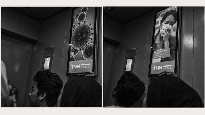 Tampilan virus Corona atau COVID-19 (kiri) dan adegan orang dengan gejala COVID-19 di sebuah layar iklan layanan masyarakat di Jakarta.