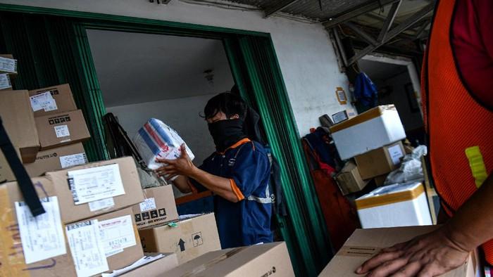 Pekerja mengangkut barang yang akan dikirim melalui kereta api di Stasiun Pasar Senen, Jakarta Pusat, Senin (30/3/2020). Jasa pengiriman logistik melalui kereta api menurun sekitar 15 hingga 30 persen sebagai imbas dari wabah COVID-19 serta adanya kebijakan pembatalan jadwal perjalanan kereta api. ANTARA FOTO/Sigid Kurniawan/foc.