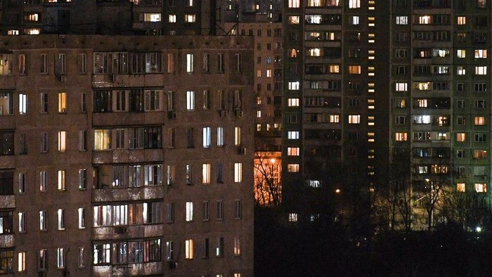Residents stay in their apartments on the Moscow outskirts late on March 29, 2020. - All residents of Moscow will be under strict self-isolation rules beginning on March 30, 2020, the mayor said in the evening of March 29, as coronavirus cases climbed in the capital. Muscovites will only be allowed to leave their homes in the case of a medical emergency, to travel to work if necessary, and go to grocery stores or pharmacies, the capitals mayor Sergei Sobyanin said in a statement. (Photo by Kirill KUDRYAVTSEV / AFP)