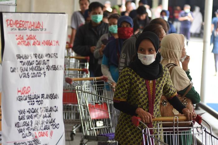 Warga berbelanja saat pemberlakuan pembatasan pengunjung supermarket di Tiptop, Depok, Jawa Barat, Senin (30/3/2020). Pembatasan jumlah pengunjung yang berbelanja tersebut untuk mencegah penyebaran COVID-19. ANTARA FOTO/Indrianto Eko Suwarso/foc.