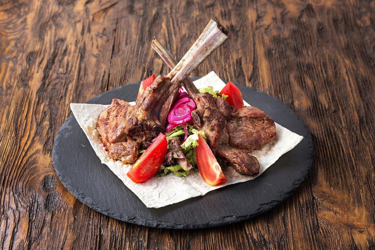 ribeye steak on the bone, tomahawk, served with tomatoes and iceberg lettuce on pita on slate board.