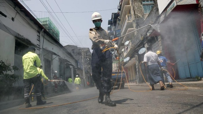 Members of the Myanmar Red Cross disinfect a street as a preventive measure against the COVID-19 coronavirus in Yangon on March 29, 2020. (Photo by Sai Aung Main / AFP)