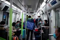 Petugas kereta berkeliling mengenakan masker dengan membawa papa pengumuman yang menghimbau warga untuk selalu pakai masker, hindari berkumpul di keramaian dan scan kode saat keluar dari kereta. (Aly Song/Reuters)
