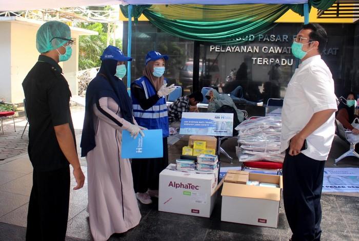 Perwakilan dari Human Initiative secara simbolis menyampaikan bantuan Alat Pelindung Diri (APD) dan Multivitamin kepada Rumah Sakit Umum Daerah (RSUD) Pasar Rebo dan RSUD Pasar Minggu, di Jakarta, Rabu (1/4/2020). PT ABM Investama Tbk menggandeng lembaga nirlaba PKPU Human Initiative untuk mendistribusikan APD berupa setelan lengkap pakaian hazmat, sarung tangan medis, masker, dan hand sanitizer serta multivitamin ke sejumlah rumah sakit rujukan Covid-19 di Jakarta dan Aceh sebagai dukungan kepada tenaga medis yang menjadi ujung tombak melawan penyebaran pandemi COVID-19.