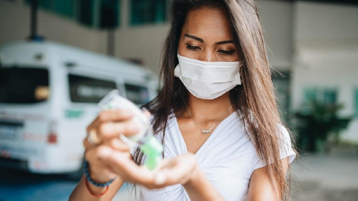 Young woman wearing face mask because of air pollution in the city