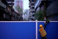 Ini foto saat tukang antar makanan memberikan paketnya meallui pagar pembatas. (Aly Song/Reuters)