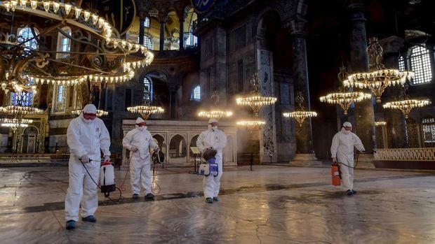 Petugas membersihkan bagian dalam Hagia Sophia dengan disinfektan (Photo by Yasin AKGUL / AFP)