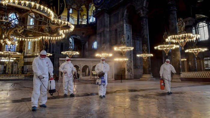 Employees of the Fatih Municipality wearing protective suits disinfect the Hagia Sophia to prevent the spread of the COVID-19, caused by the novel coronavirus, in Istanbul, on March 13, 2020. - Turkey announced on March 11, 2020 its first coronavirus case, a man who had recently travelled to Europe and is in good health. Turkey has announced several measures in recent weeks to try and stop the virus reaching the country, including thermal cameras at airports, cancelling flights to affected countries and closing its border with Iran. (Photo by Yasin AKGUL / AFP)