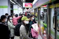 Kereta bawah tanah pun juga mulai beroperasi. ORang-orang masih mengenakan masker saat di stasiun. (Aly Song/Reuters)