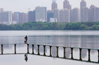 Terlihat sepasang sijoli menikmati waktu di Ewas Lake di Wuhan. Mereka berpelukan namun tetap keduanya memakai masker. (Aly Song/Reuters)