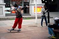 Seorang pria bermain skateboar dan tetap mengenakan masker. (Aly Song/Reuters)